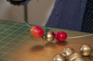Stringing berries onto ribbons to make home crafted Xmas decorations